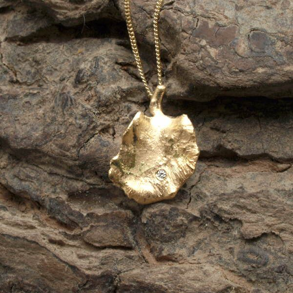 18ct gold and diamond leaf pendant on wood